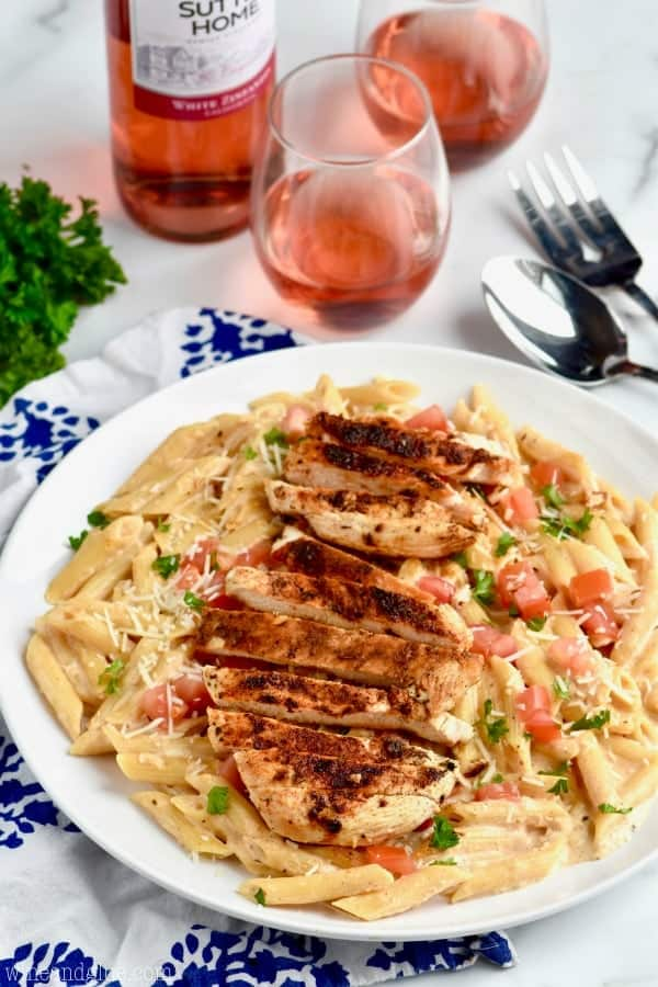 side view of a plate of creamy cajun chicken pasta, an easy chicken recipe garnished with fresh parmesan, parsley and diced tomatoes with two glasses of wine in the background