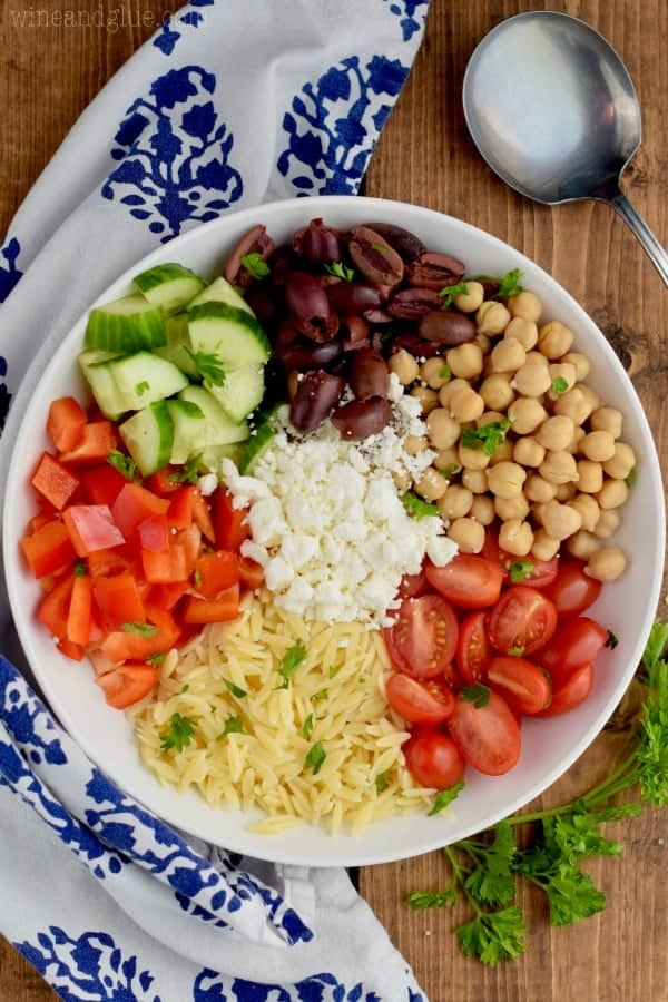 An overhead photo of a white bowl with the ingredients of the Easy Orzo Pasta Salad which is not mixed. (Orzo, red peppers, cucumbers, olives, chickpeas, and cherry tomatoes)