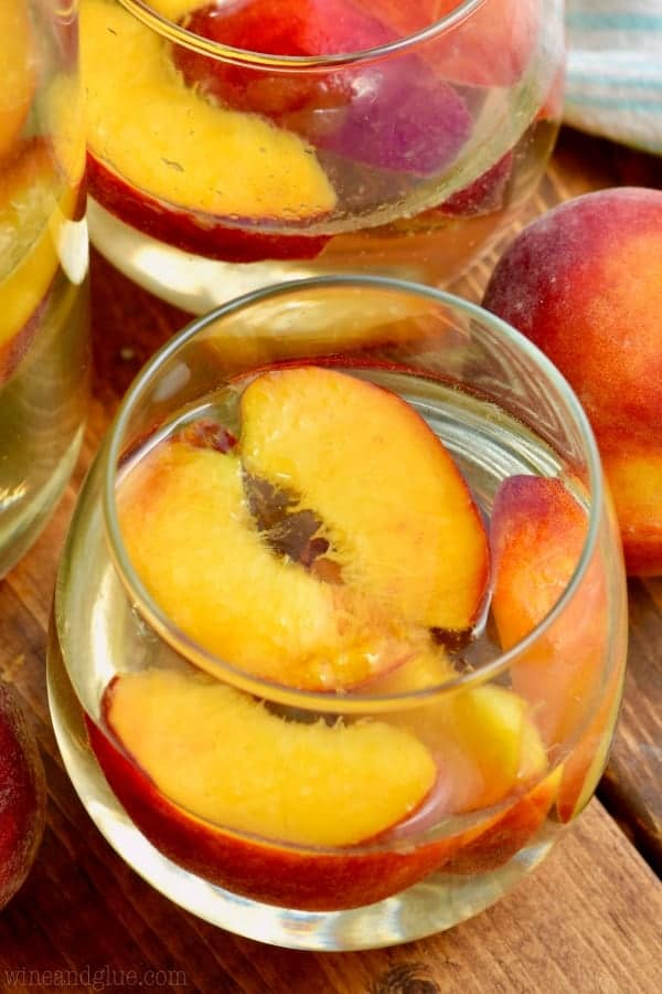 glass of peach sangria with fresh peaches in it