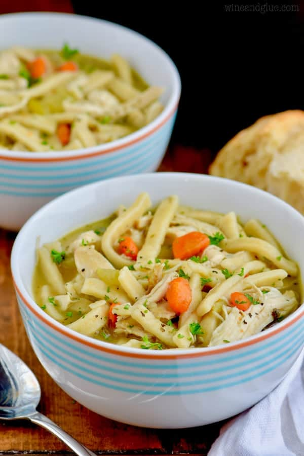 The Homemade Chicken Noodle Soup is in a small bowl and topped with ground black pepper and parsley.