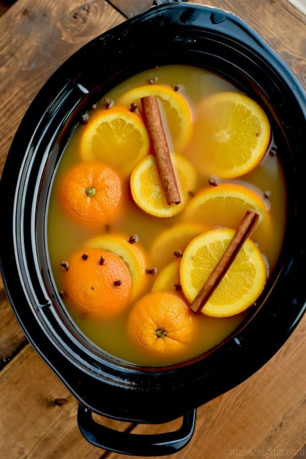 overhead view of a crockpot to make spiced apple cider filled with orange slices studded with cloves and cinnamon sticks