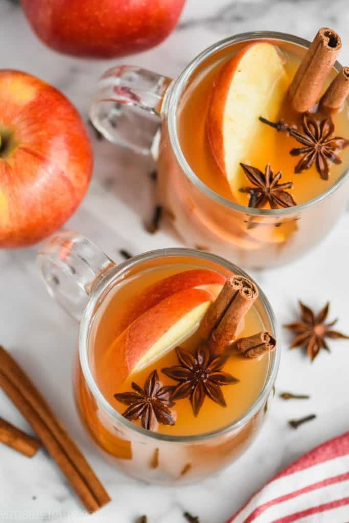 overhead view of two clear mugs full of crockpot spiced apple cider and garnished with star anise, sliced apples and cinnamon sticks