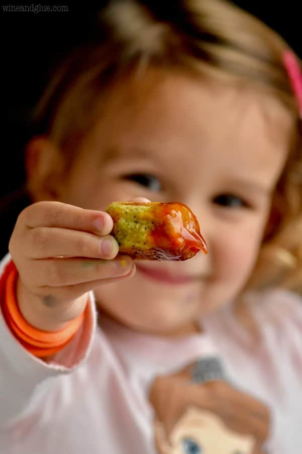 A little girl holding a Broccoli Cheddar Cauliflower Tator Tot dipped into ketchup.