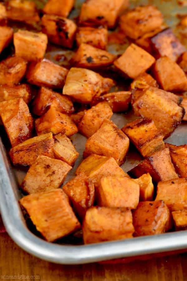 brown sugar roasted sweet potatoes cubed on a silver baking sheet