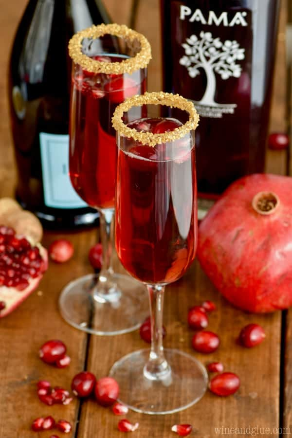 Two flukes of Cranberry Pomegranate Champagne Cocktails with gold sprinkles on the lip of the glass.