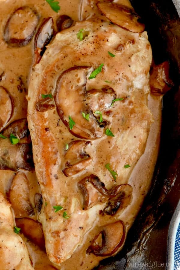 close up of a chicken breast in easy chicken marsala in a frying pan covered in sauce and mushrooms