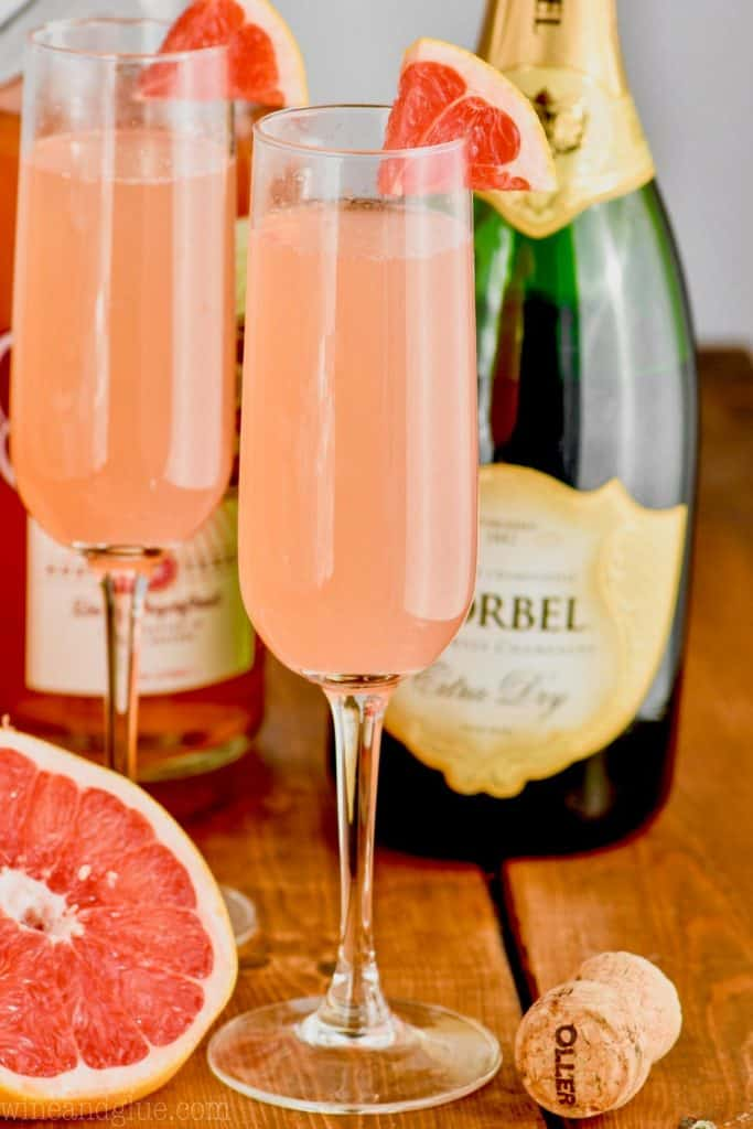two champagne glasses filled with grapefruit champagne cocktail garnished with small wedges of fresh grapefruit, a half of a grapefruit in the background and a bottle of champagne