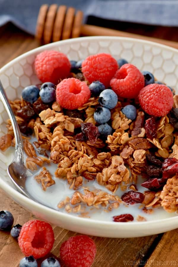 bowl of homemade granola with milk, a spoon, fresh raspberries and blueberries