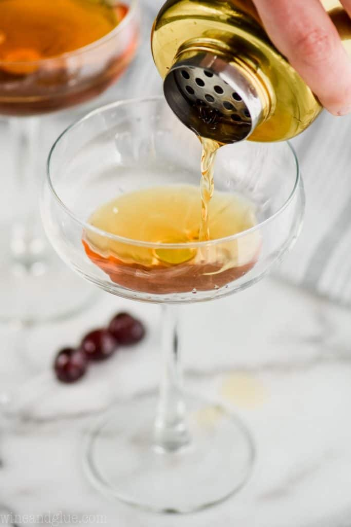 a Manhattan cocktail being strained into a champagne coupe glass