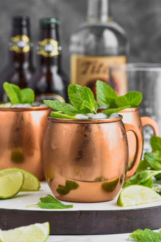 moscow mule ingredients behind a copper mug filled with a moscow mule, mint, and lime