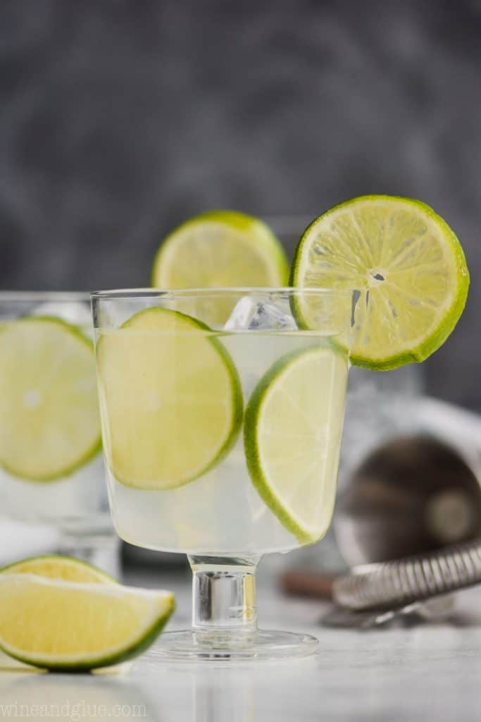 small goblet with lime slices in it and a vodka gimlet recipe, garnished with a lime slice, another glass in the background and a lime wedge in the forefront