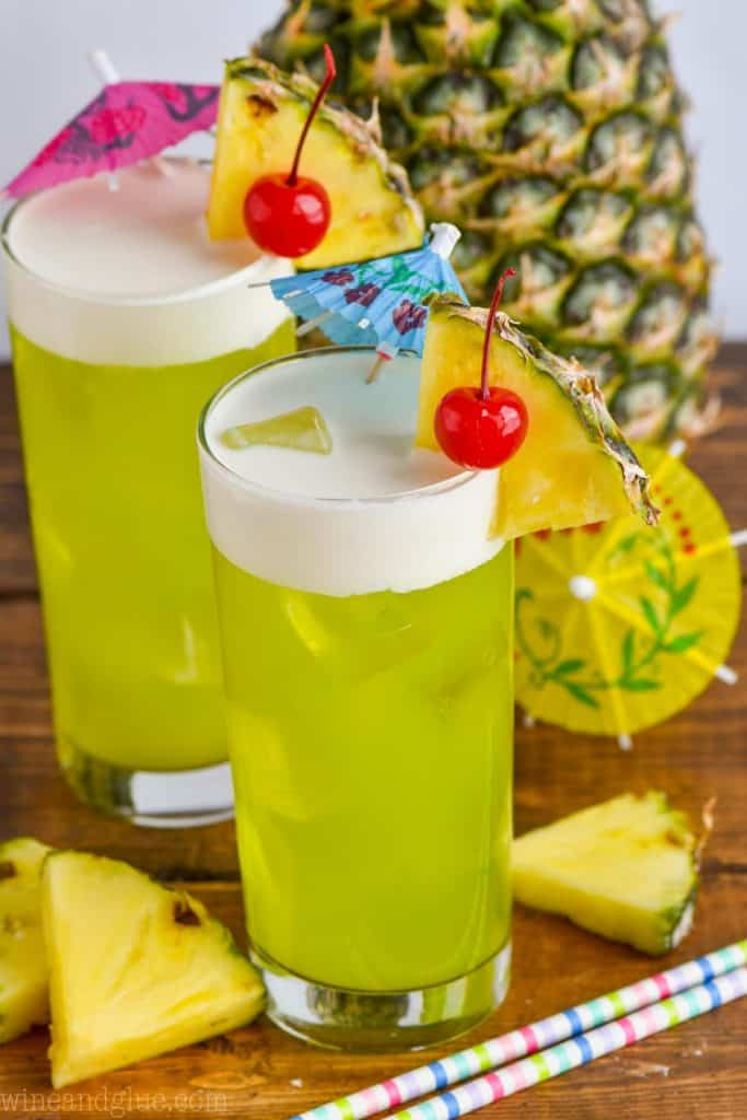 two glasses of midori splice garnished with maraschino cherries and pineapple slices