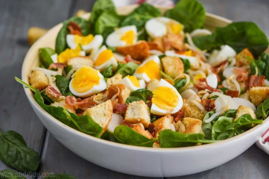 white bowl filled with spinach salad with bacon hard boiled eggs and croutons on a blue wood board