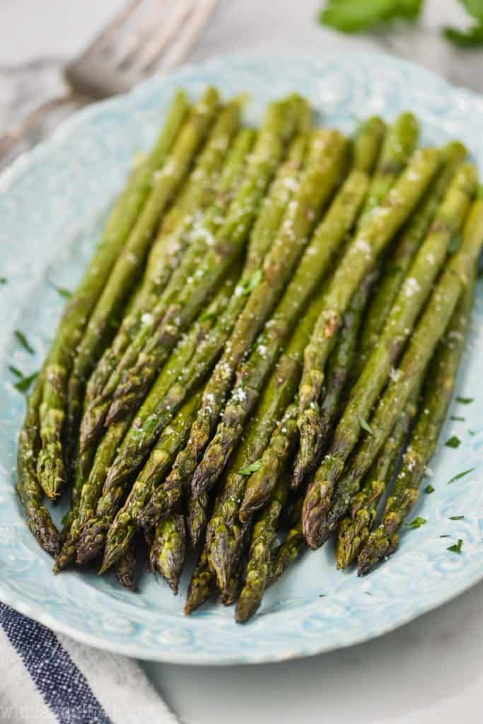 oven baked asparagus soon a blue platee sprinkled with parsley and parmesan