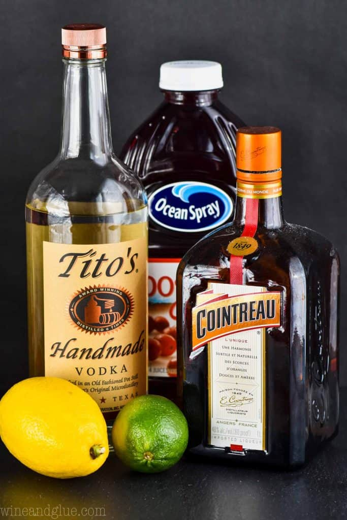 a bottle of titos, a bottle of ocean spray cranberry juice, and a bottle of cointreau with a lemon and lime against a black background - the ingredients for a cosmopolitan cocktail