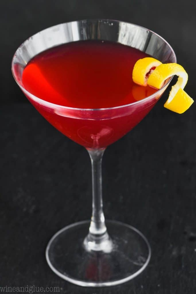 overhead view of martini glass holding a cosmopolitan cocktail recipe against a black background with a lemon twist as a garnish