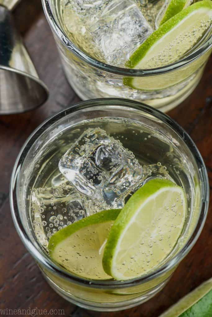 overhead view of a tumbler full of a gin and tonic recipe filled with ice and two lime slices on a wood table