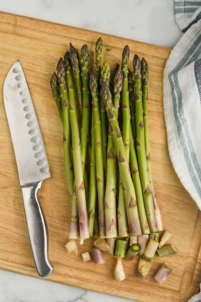 a bunch of asparagus on a cutting board with a small amount cut off the bottoms