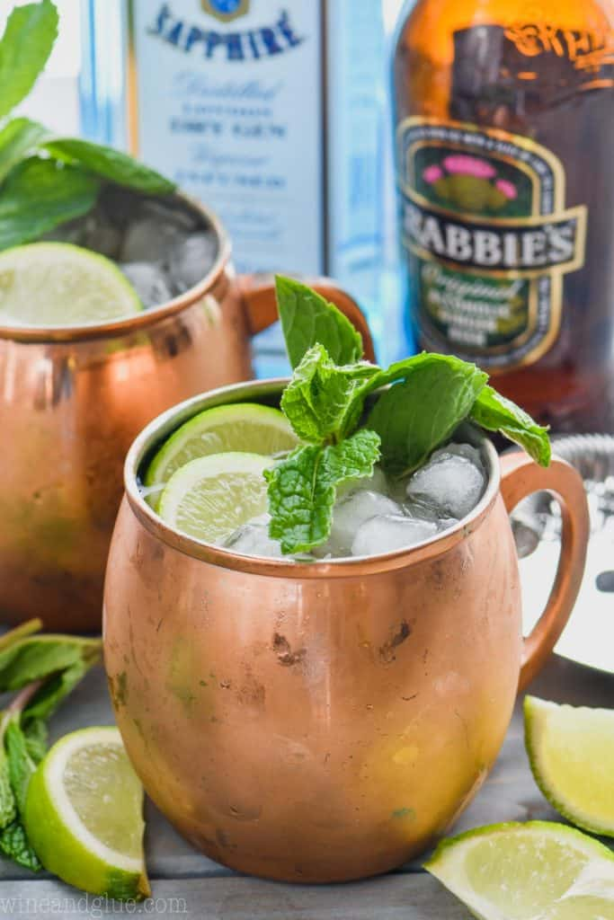 gin moscow mule in a copper mug with a bottle of gin and ginger beer in the background, lime wedges laying next to the mugs