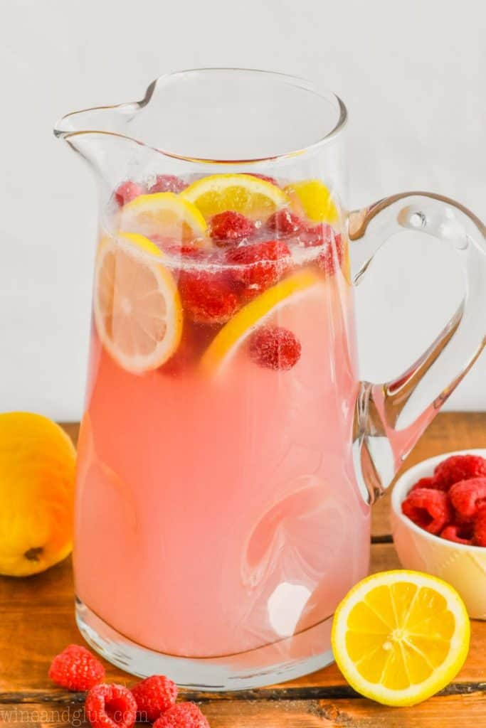 pitcher full of pink lemonade vodka punch floating with fresh raspberries and lemon slices