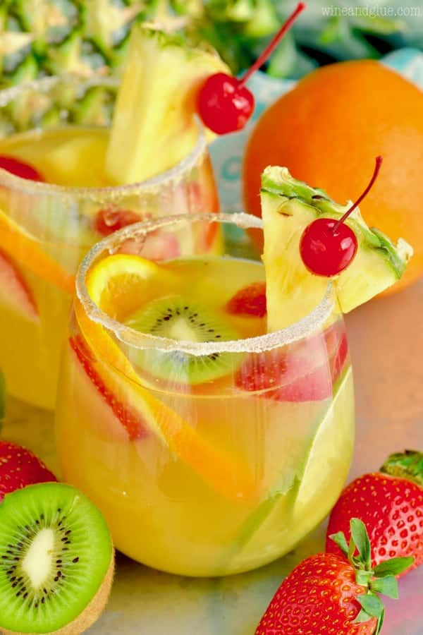 glass of tropical margarita sangria with a pineapple wedge and a cherry