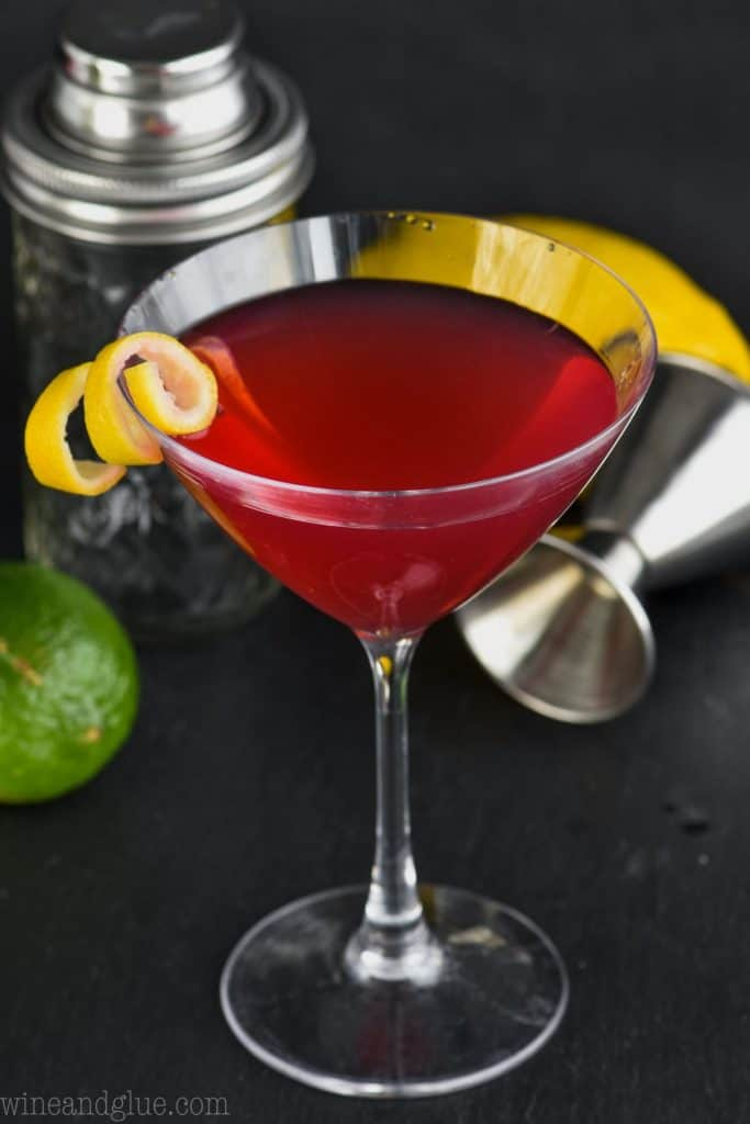overhead view of a martini glass holding a cosmopolitan cocktail recipe with a lemon twist garnish and a cocktail shaker, lime, and lemon in the background