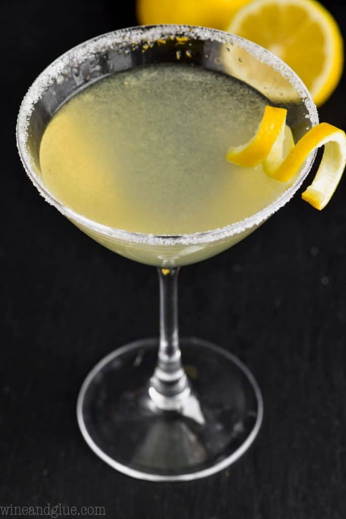 overhead view of a martini glass, rimmed with sugar, full of a lemon drop martini, garnished with a lemon curl with lemons in the background on a black background