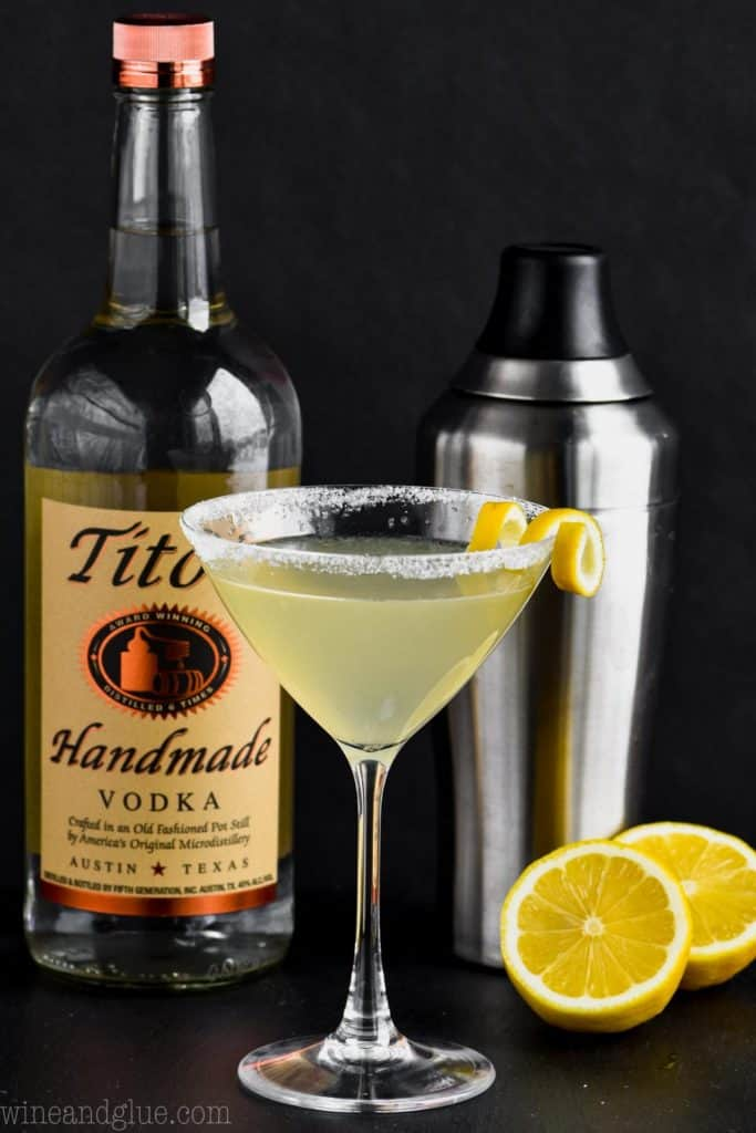 martini glass filled with a lemon drop martini, rimmed with sugar, garnished with a lemon curl infront of a bottle of titos and a martini shaker