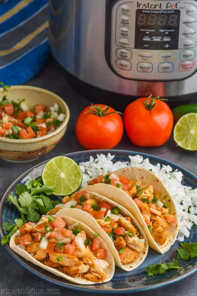 three pressure cooker chicken tacos on a plate with an instant pot