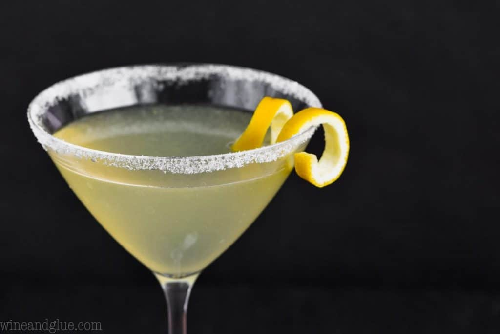 a land scape photo of the top half of a martini glass rimmed with sugar, full of a lemon drop martini recipe, and garnished with a lemon curl on a black background