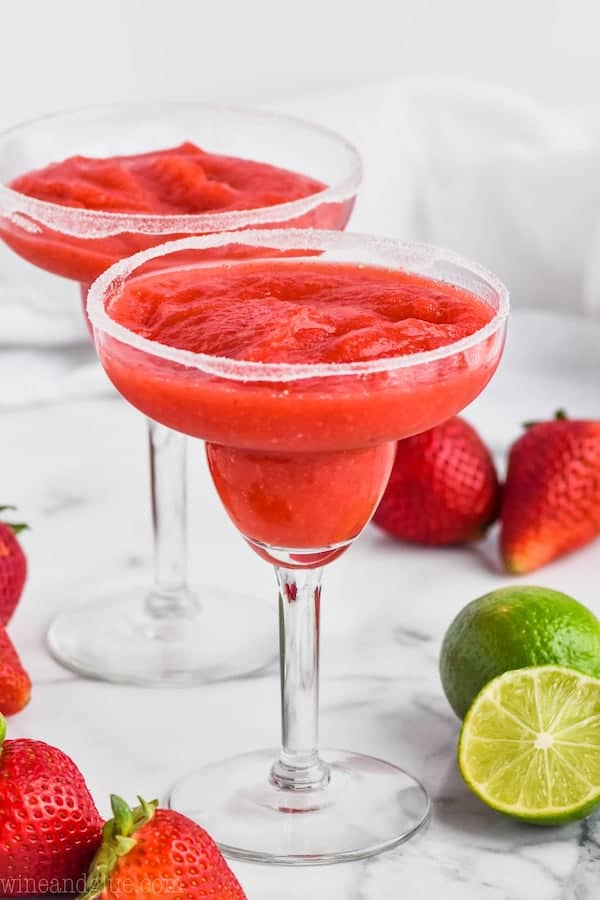 two margarita glasses rimmed with sugar and filled with strawberry margaritas surrounded by strawberries and limes
