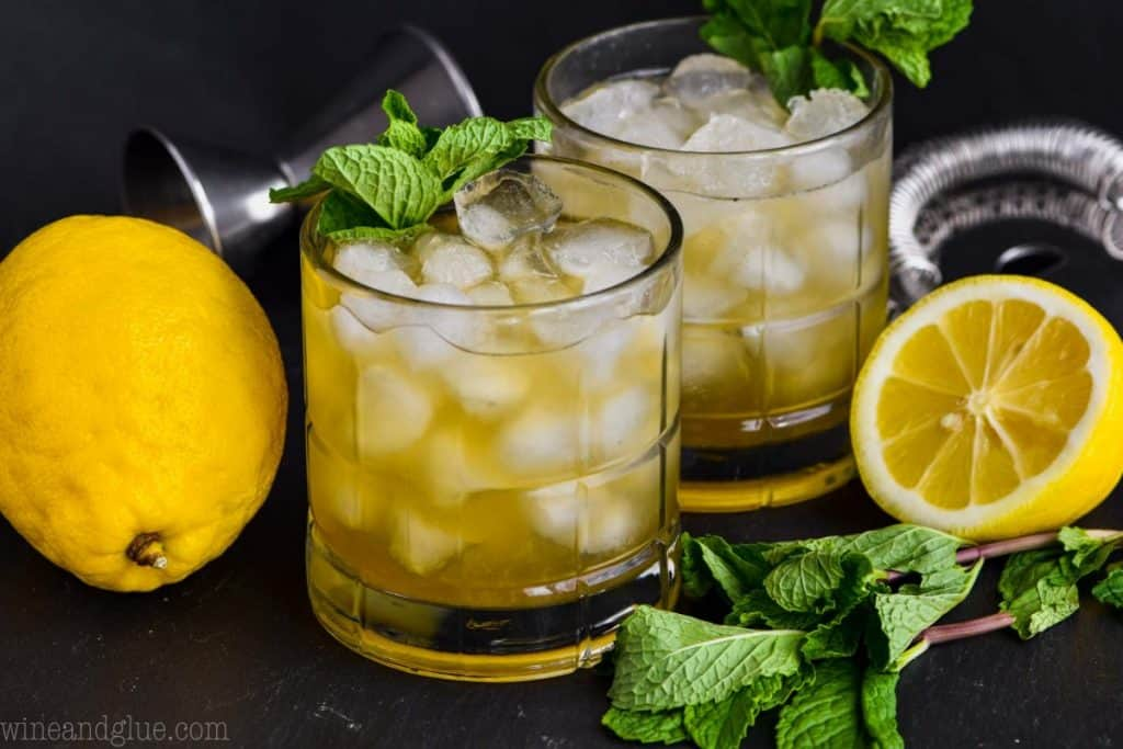 two small tumblers filled with ice, whiskey smash cocktail, and garnished with fresh mints, a full lemon on one side, a half lemon the other side and fresh mint sprig lying in front