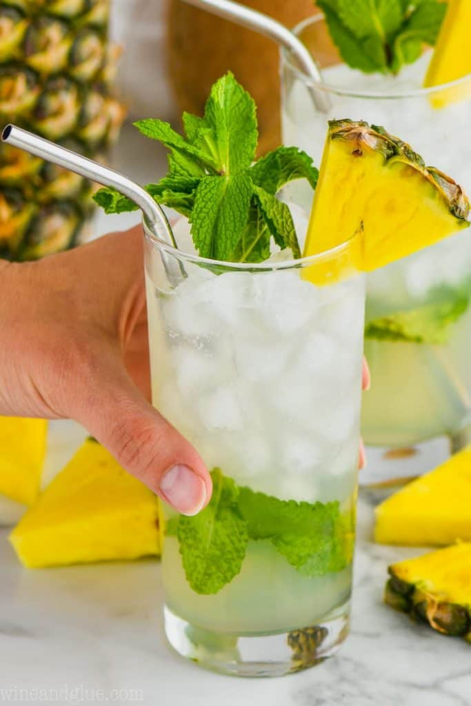 hand holding high ball glass filled with ice and a pineapple mojito, garnished with mint and a pineapple wedge