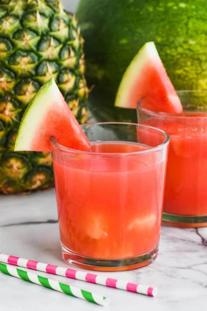 two small tumblers straight on with watermelon pineapple rum punch and garnished with watermelon wedges