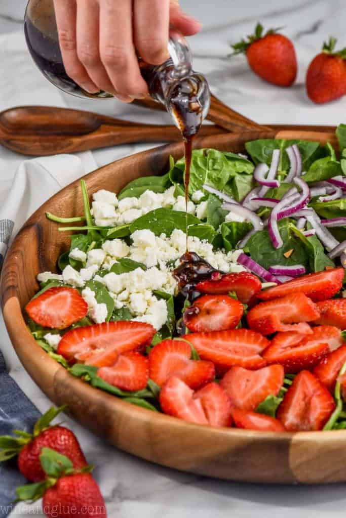 side view of strawberry spinach salad with balsamic poppyseed dressing being poured on it