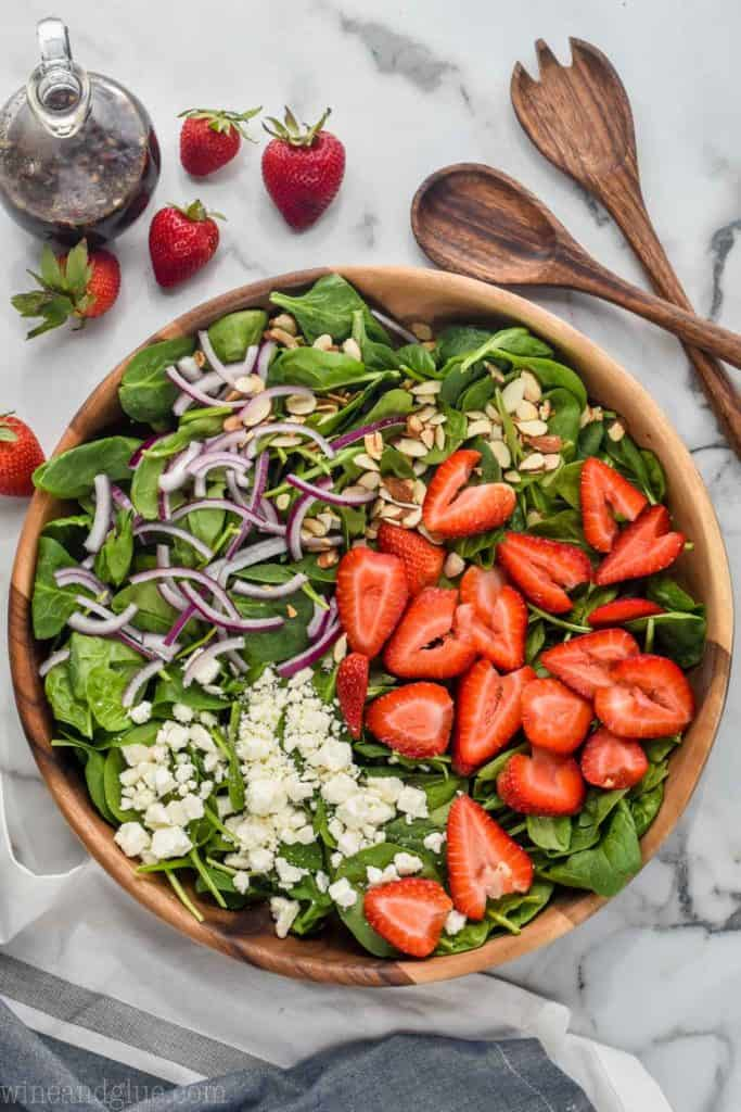 overhead view of spinach strawberry salad with red onions, toasted almonds, and feta cheese