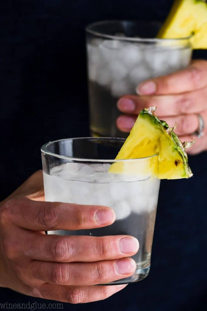 woman holding two pina colada vodka sodas in front of a dark shirt, garnished with pineapple wedges