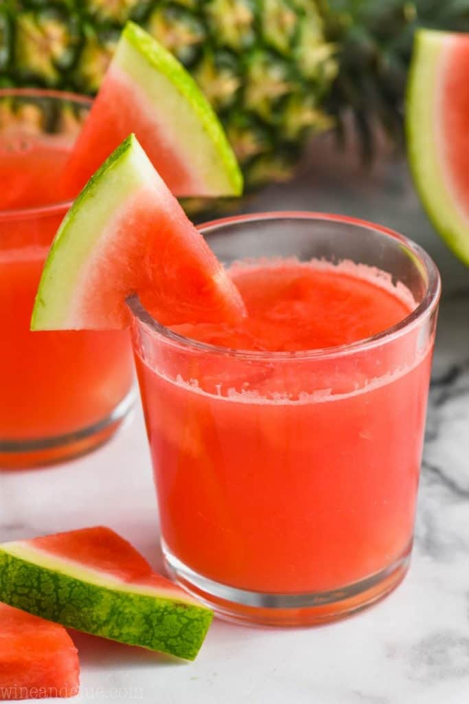 small tumbler glass filled with rum punch and garnished with a watermelon wedge, a pineapple and another glass of punch in the background