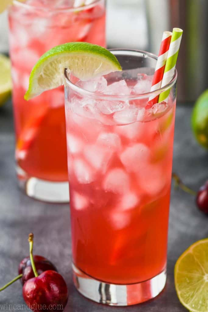 high ball glass full of cherry lime vodka tonic garnished with a lime wedge