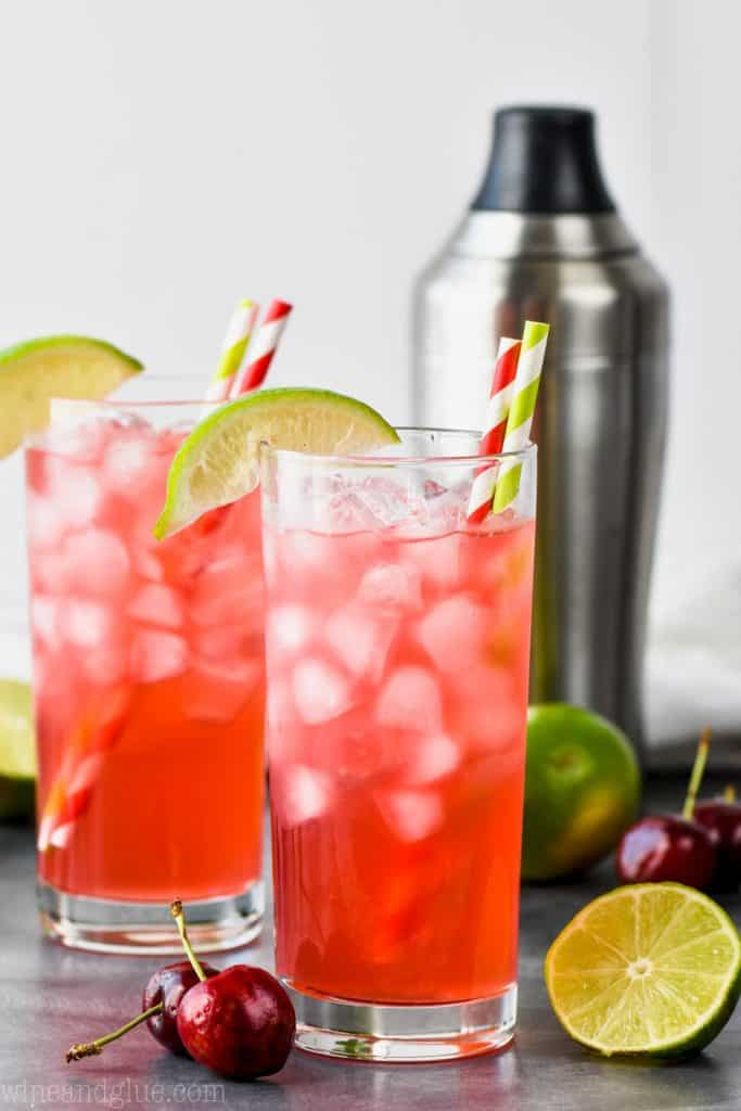 two high ball glasses with a cocktail shaker in the background filled with ice and cherry limeade recipe