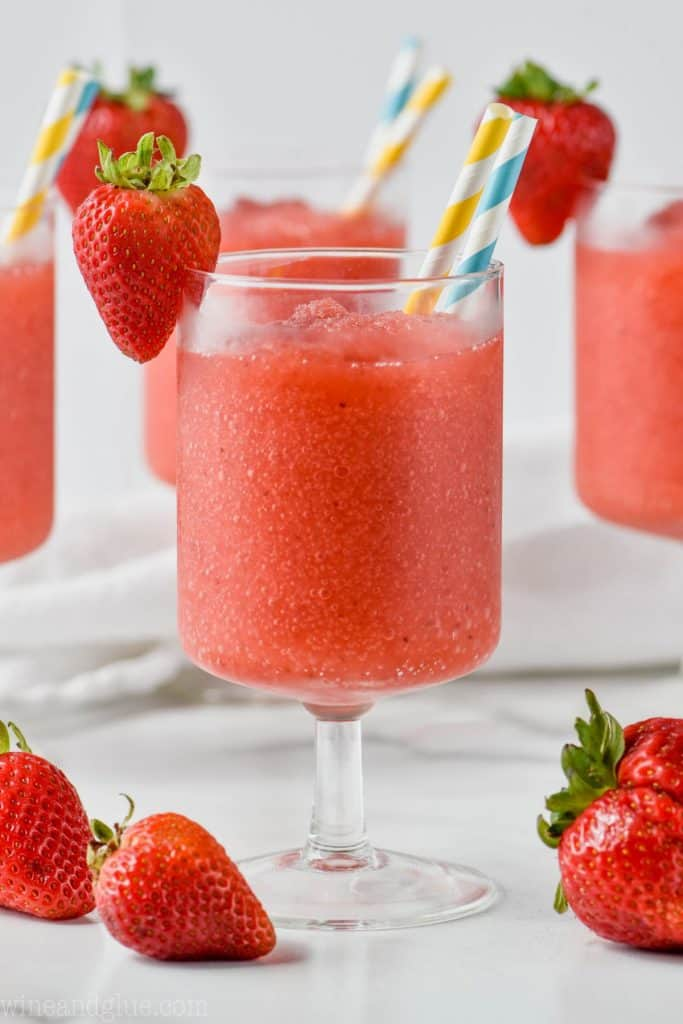 face on view of glass of frose with straws and garnished by strawberries