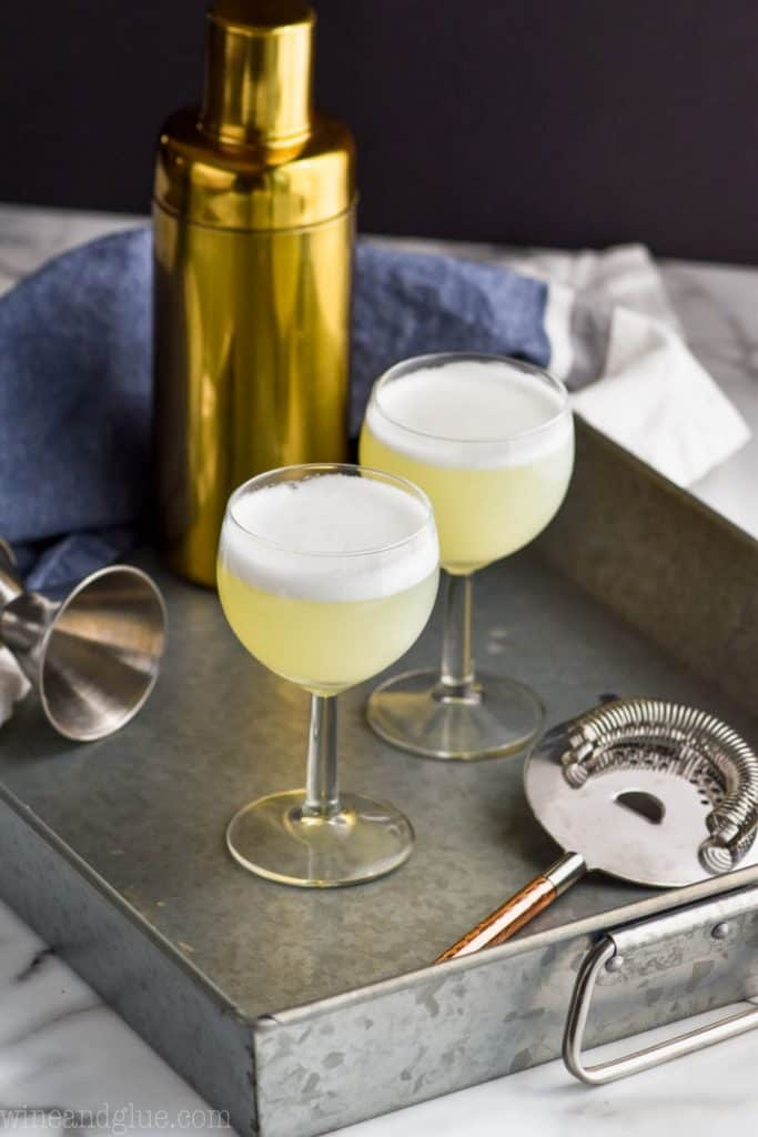 two small wine glasses filled with gin fizz egg white recipe on a metal tray with a strainer and a gold shaker
