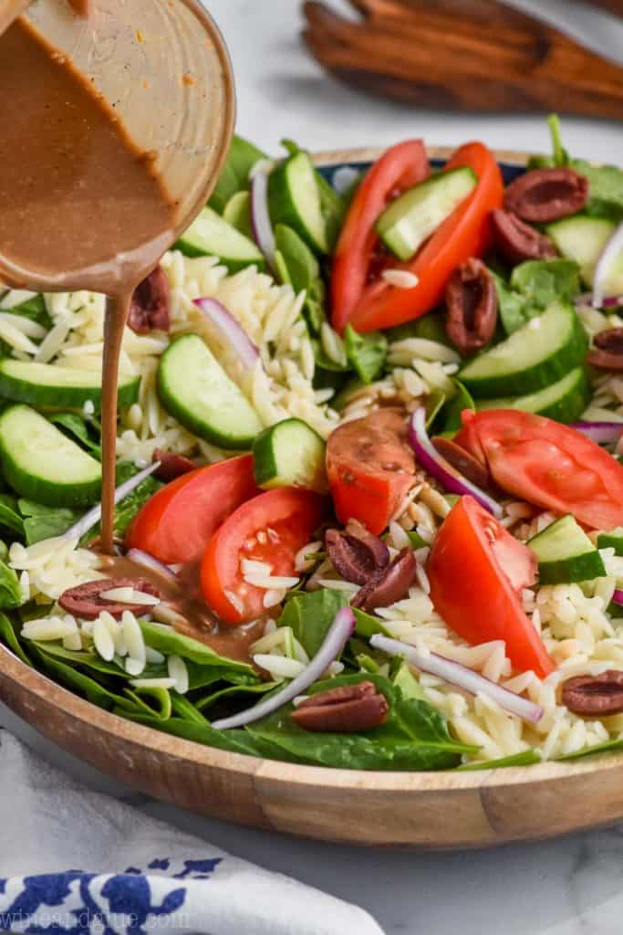 bowl of orzo pasta salad with creamy balsamic dressing being poured over it.