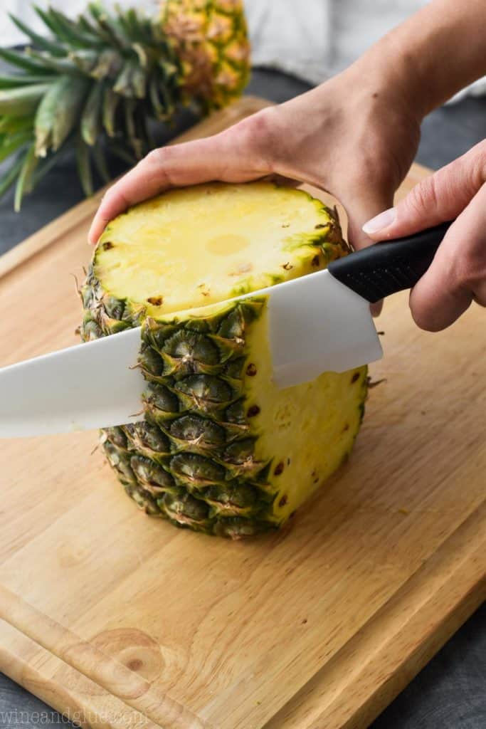 a pineapple on a cutting board with the skin being cut off
