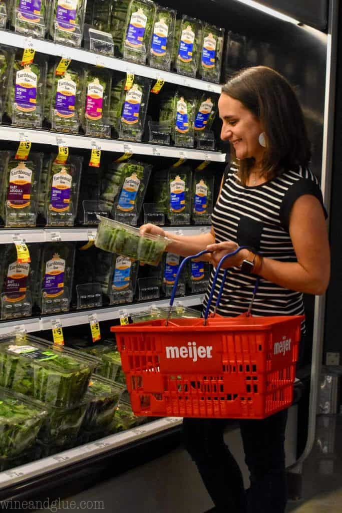 woman holding baby spinach in a grocery store