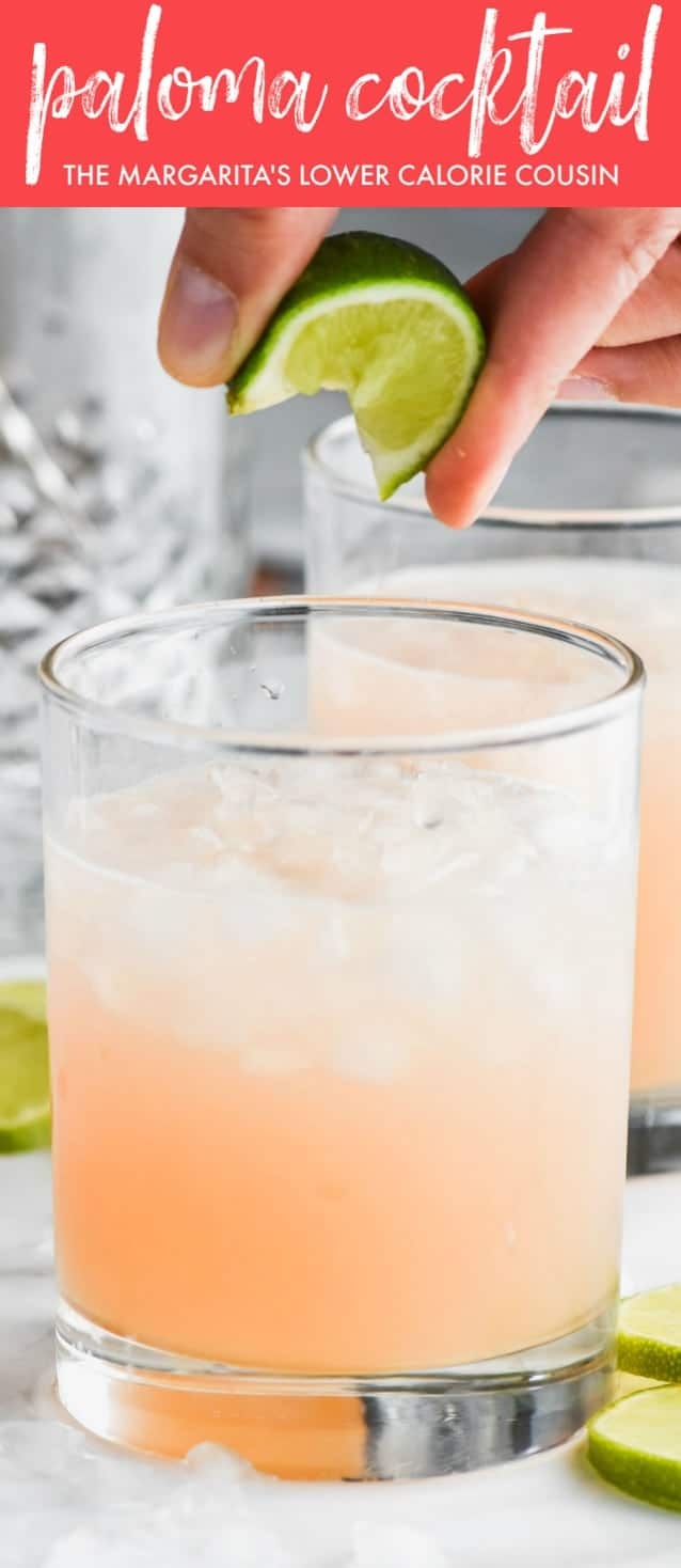 closes up of fingers squeezing a lime wedge into a tumbler half filled with ice and a paloma cocktail