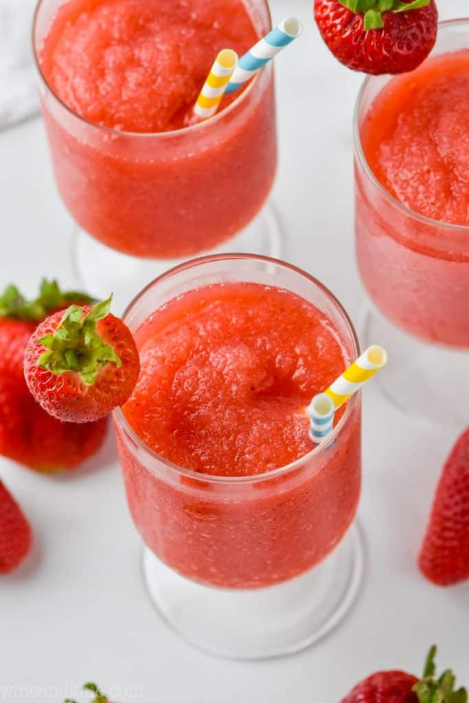 overhead view of three glasses of frozen frose garnished with strawberries