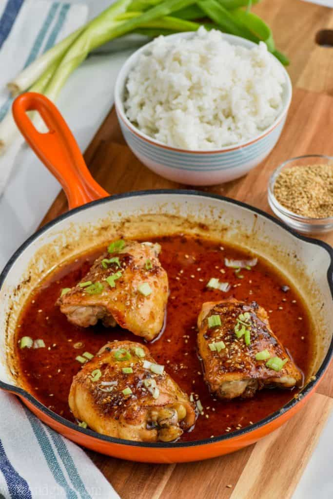 the best honey garlic chicken in a pan with a bowl of rice behind it