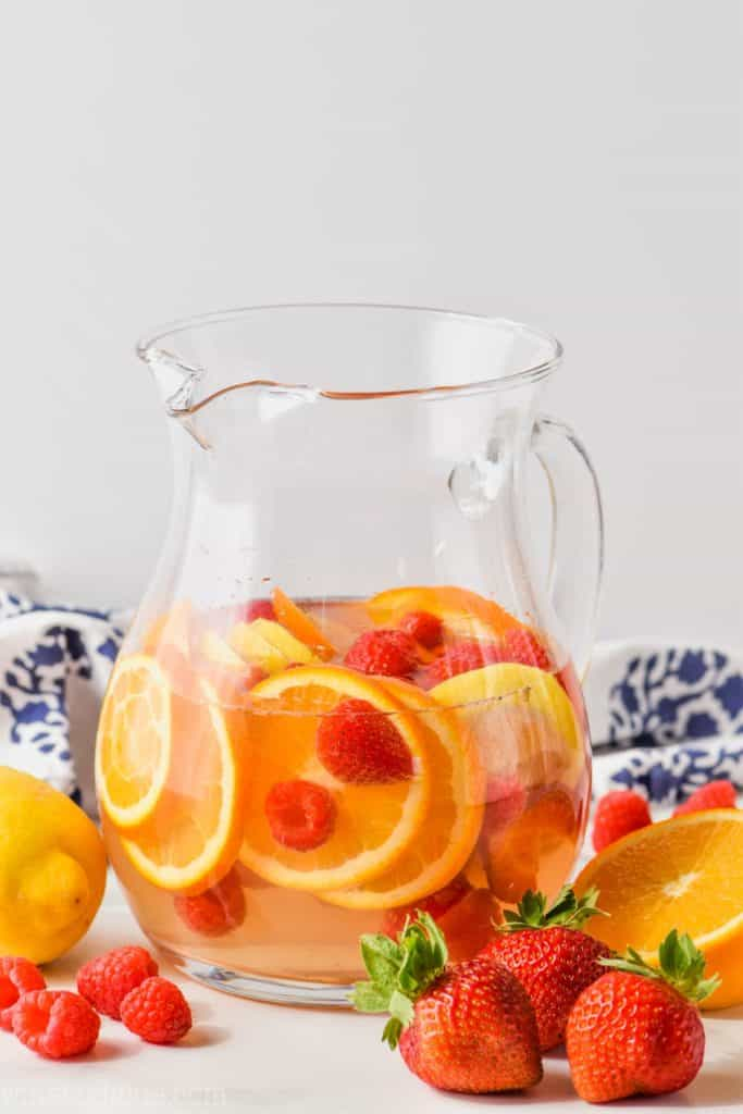 pitcher of easy white wine sangria recipe with raspberries, strawberries, oranges, and lemons