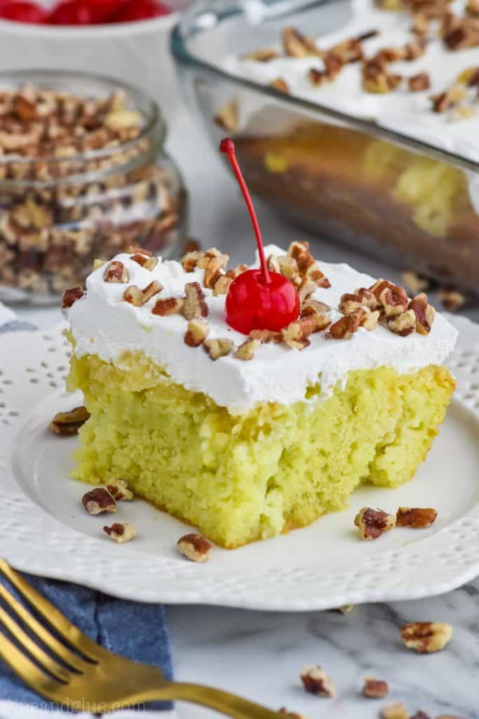 watergate cake recipe on a plate topped with walnuts and a cherry
